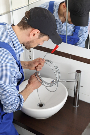 A Plumber cleaning a pipe drain with a Spiral