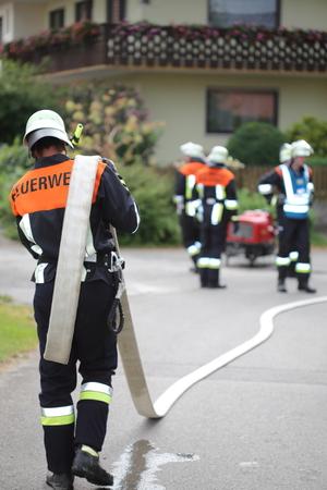 Ein Feuerwehrmann mit Schlauch über die Schulter Schultern Standard-Bild - 61939399