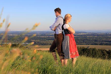 Ein deutsches Paar in bayerischer Kostüm zurück auf Gras an Rücken Standard-Bild - 61222436