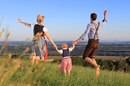 Eine deutsche Familie in bayerischer Tracht glücklich Wiese springen Standard-Bild