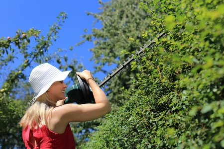 electric trimmer: A Woman hedge cutting with summer hat Stock Photo