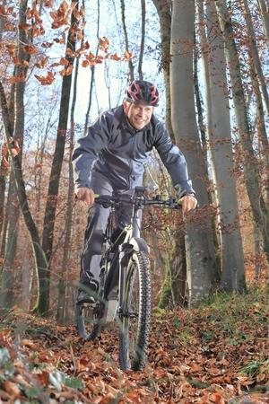 Ein Älterer am Mountainbike im Wald Standard-Bild - 61629131