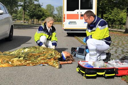 emergencia: Dos paramédicos ayudar a una mujer después de un accidente de tráfico