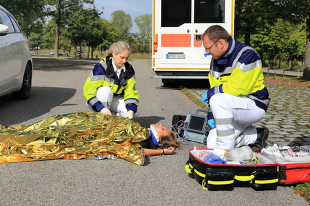 Twee paramedici het helpen van een vrouw die na een verkeersongeval