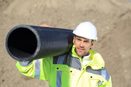 Un trabajador de la construcción con un tubo en el hombro