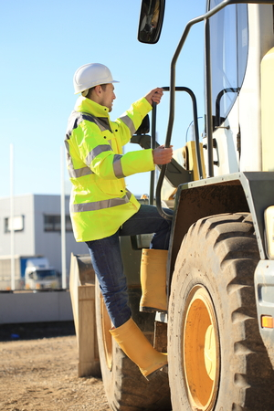 housing crisis: A Construction worker climbing a wheel loader Stock Photo