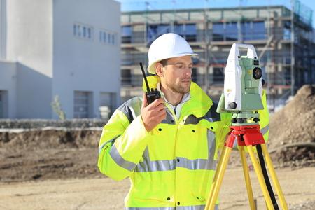 Ein Surveyor mit Vermessungsinstrument und Radio vor einem neuen buillding Standard-Bild - 65848241