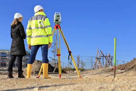 A Architect and surveyor on a construction site back sight