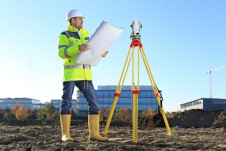 Ein Surveyor auf einem Hügel Sie einen Plan Rolle in Händen halten Standard-Bild - 65797176