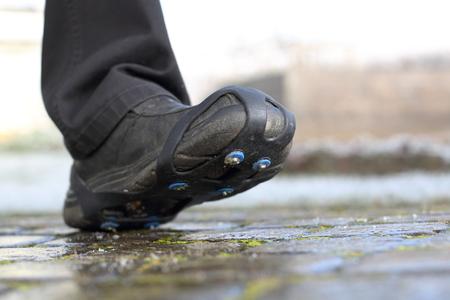 Shoe snow spikes chains on path Standard-Bild