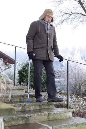 bajando escaleras: Un anciano con muletas en las escaleras heladas en invierno