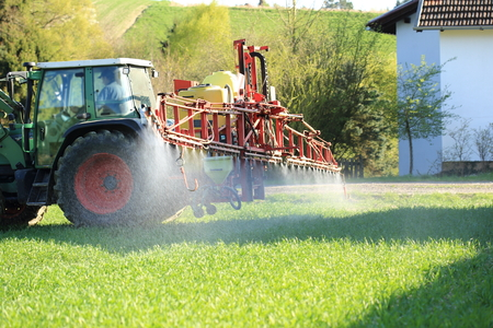 A Tractor spraying pesticide near houses Standard-Bild