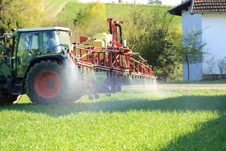 Un tractor pulverizando pesticidas cerca de las casas Foto de archivo - 76970781