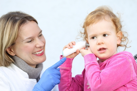 A Doctor measuring with InfraredThermomete temperature  a Child photo