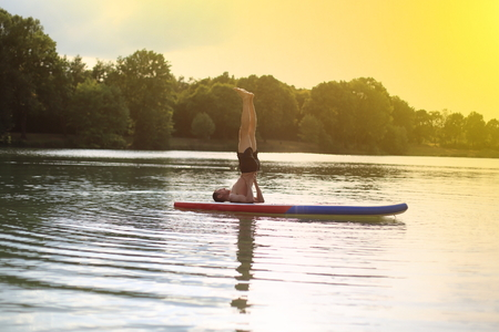 Yoga at stand up paddling SUP shoulder stand Stock Photo