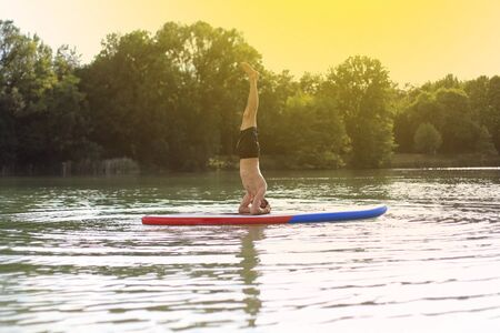 SUP yoga at  stand up paddling headstand photo