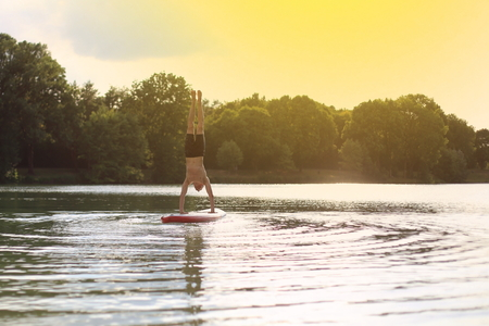 SUP yoga at stand up paddling handstand photo