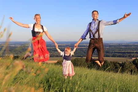 ババリア地方のドイツ家族はジャンプをドレスアップ幸せ