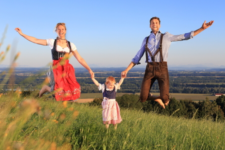 A German Family in Bavarian dress jumping happy