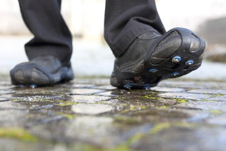 Paar Schuhspitzen-Schneeketten eine vereiste Straße im Winter Standard-Bild - 88684359