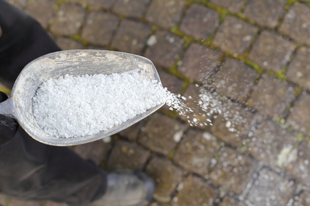 A Man spreading de-icing salt on a path in winter