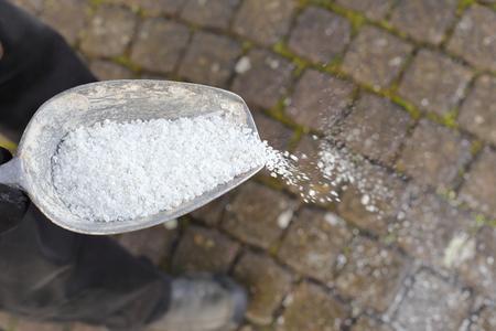 Un uomo che spande il sale antigelo su un sentiero in inverno Archivio Fotografico - 88684360