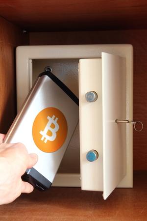 Man puts external hard drive with Bitcoin in safe Standard-Bild - 90702411