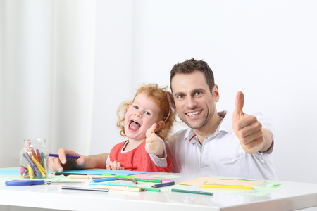 A Dad or father with child or daughter painting thumbs up
