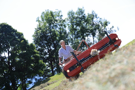 A Mountain farmer haymaking working hard Standard-Bild - 98550781