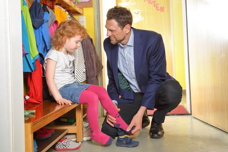 A father picks up his child in nursery Standard-Bild - 101252195