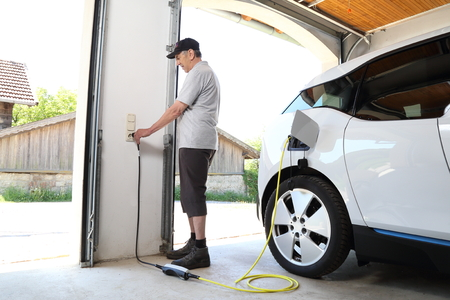 Ein Mann, der Elektroauto an der Steckdose zu Hause auflädt Standard-Bild