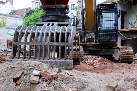 A Demolition of a house with big machine Imagens