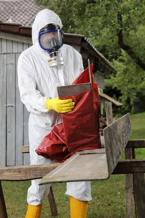 Un trabajador con máscara de embalaje Eliminación de amianto Foto de archivo