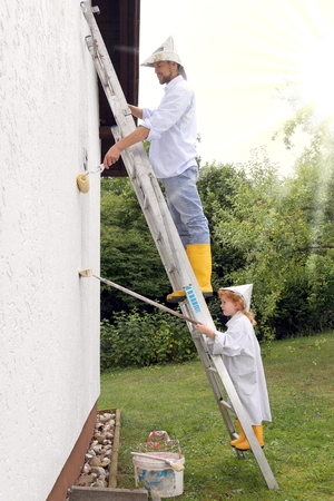 A Father and Daughter painting a house on a ladder Standard-Bild - 119226700