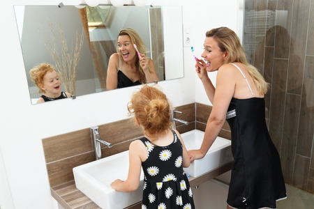 Mother and Daughter having fun during brushing teeth in a modern Bathroom Standard-Bild - 119226508