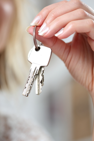 A Keychain with various keys in a womans hand Standard-Bild - 119226621