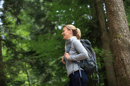 A Happy Woman hiking in a forest Standard-Bild - 119225689