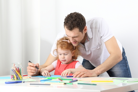 A male educator or a vather doing painting together Standard-Bild - 119225898
