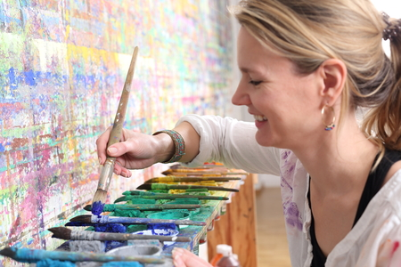 A Creative mindful woman painting with color palette Standard-Bild - 119225961