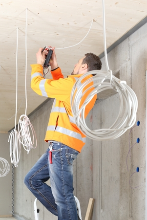 A  Electrician working in New building with cables Standard-Bild - 121545877