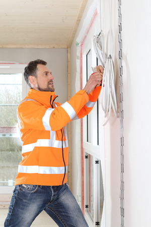 A Craftsman working in a New building as a Electrician Standard-Bild - 121545881