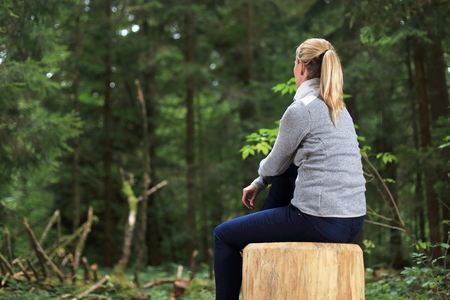 A Woman relaxed on a tree trunk in a forest Standard-Bild - 121545883
