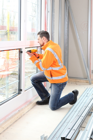 A Worker Man installing a wooden window on construction site