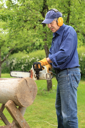 A Man working with a electric driven Chainsaw