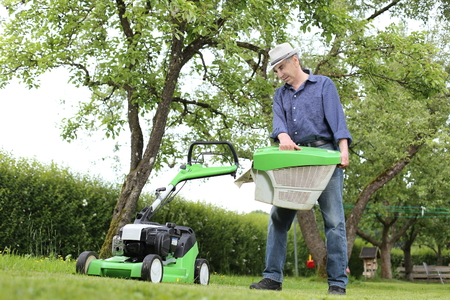 A Man working on a Lawn mower with basket