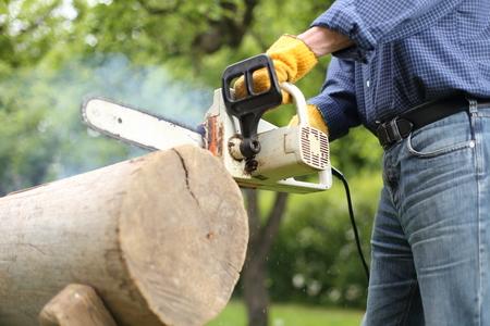 Uomo al lavoro con una vecchia catena smussata di una motosega