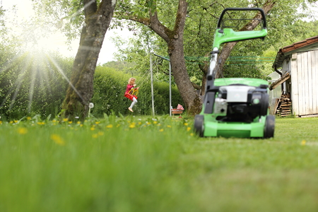 A Child playing on a swing behind a lawnmower