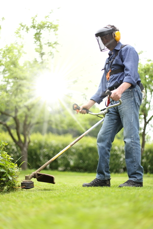 A Man working with a Brushcutter in his garden