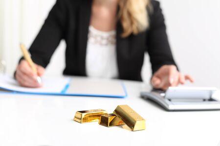 Woman with Gold Bar bullion and calculator Banco de Imagens