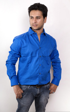 streight: young indian male model in blue shirt side pose